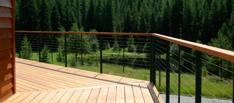 Green cable railing posts with wood hand rail.