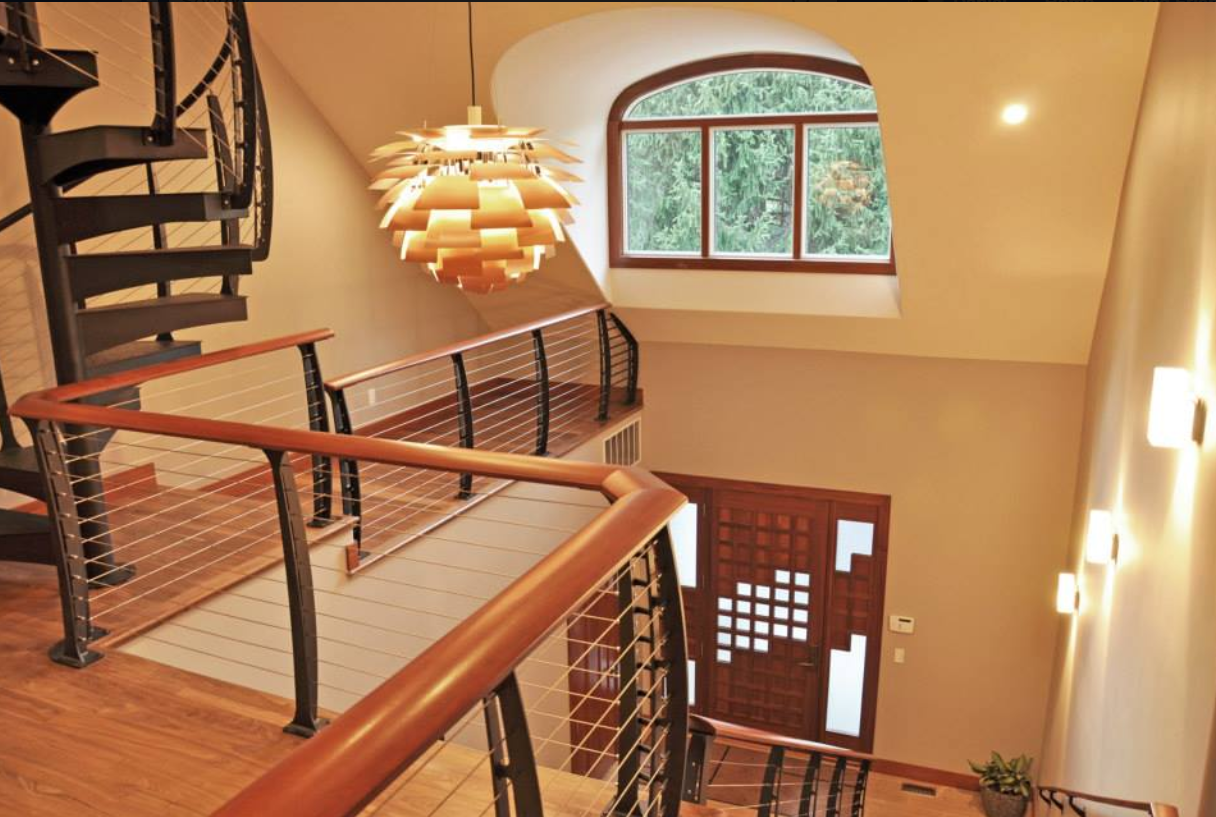 Grand entry with modern spiral staircase and balcony cable railing