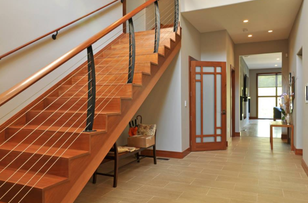 Curved staircase cable railing on in modern home entrance