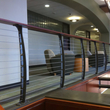 College staircase with curved cable railing and stainless steel graspable ADA railing