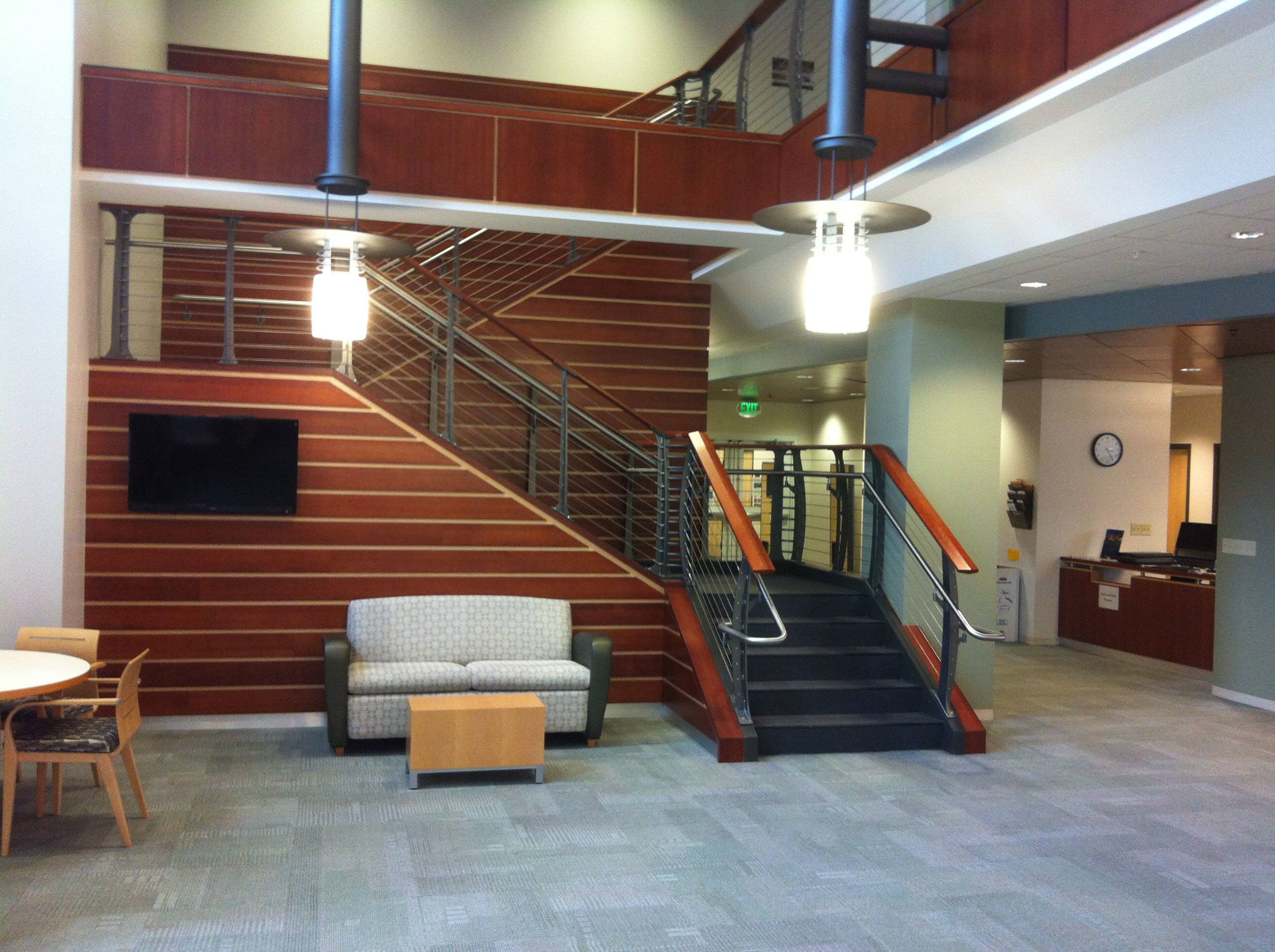College staricase with stainless ADA handrail and teak and holly style paneling