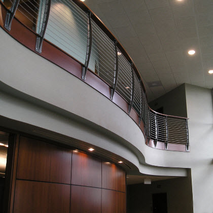 Curved second story loft with the curved Keuka style curvaceous cable railing.