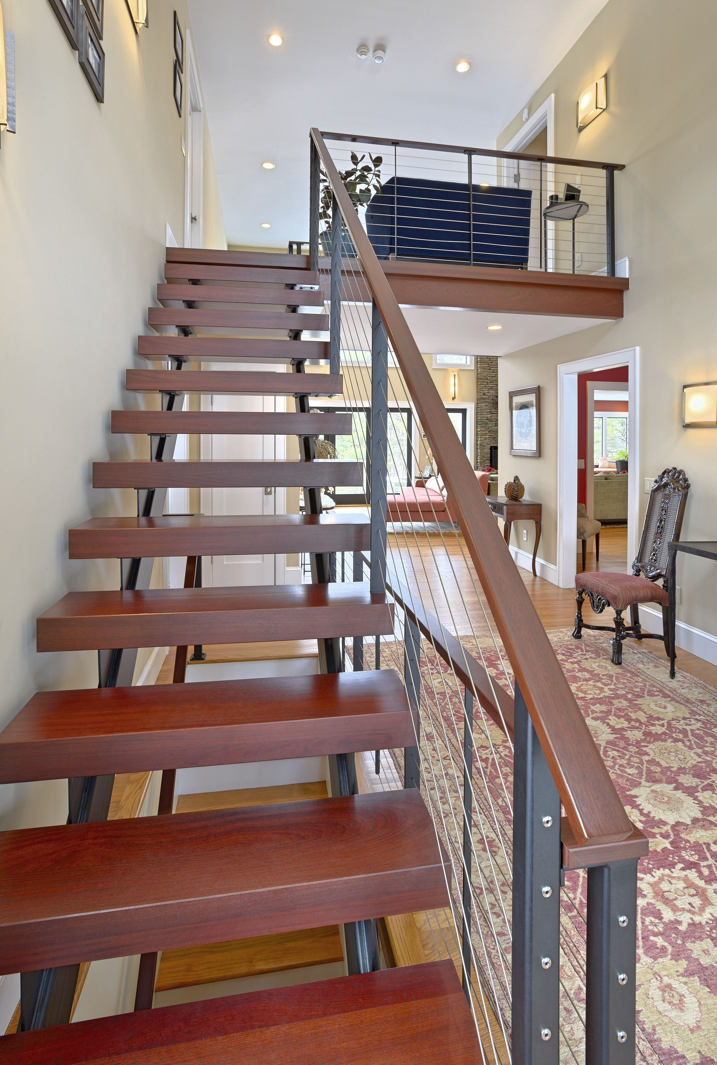 Double stringer floating staircase with cable railing and wood treads