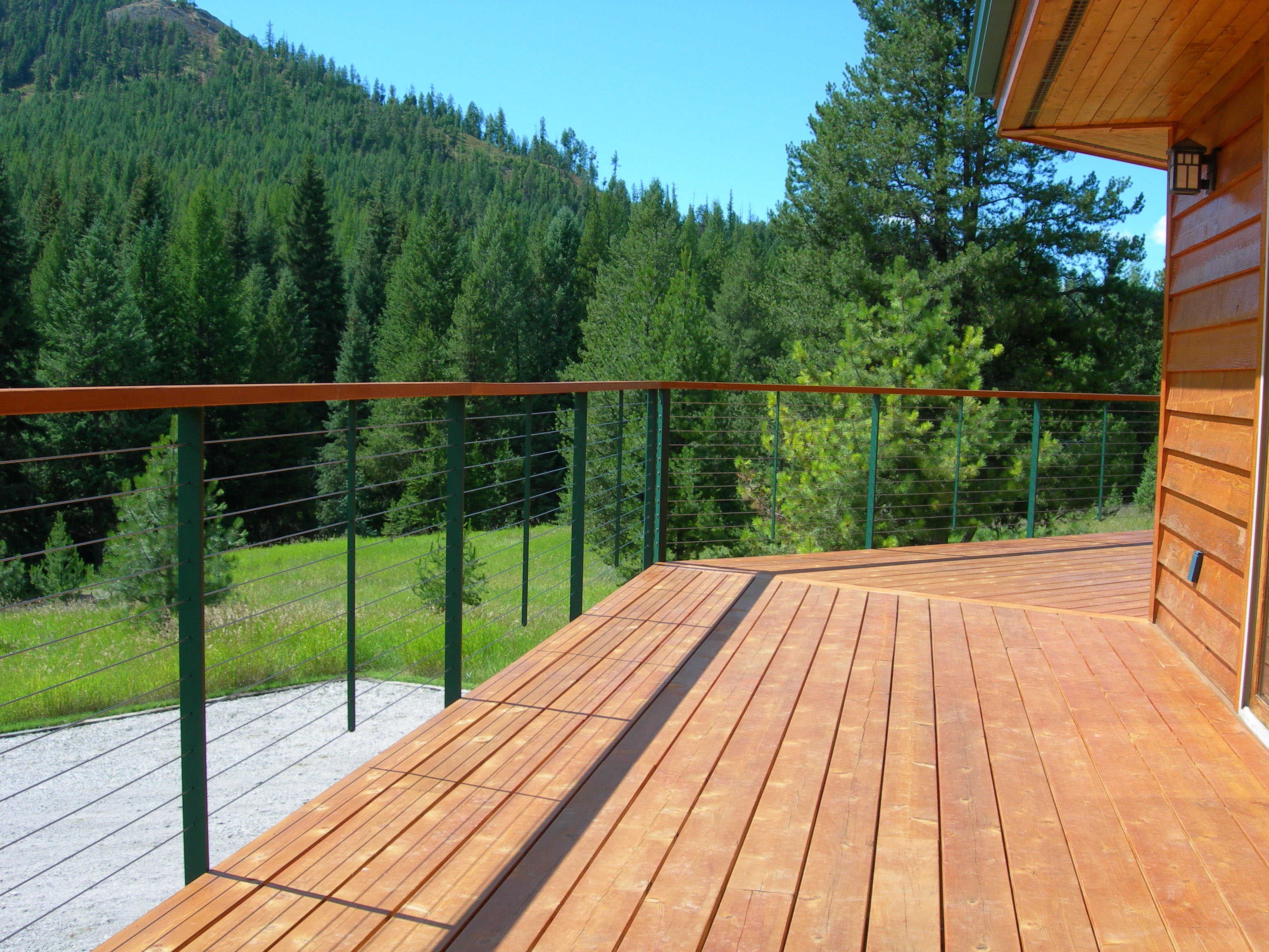 Green metal railing posts and wood top rail complement the forest view