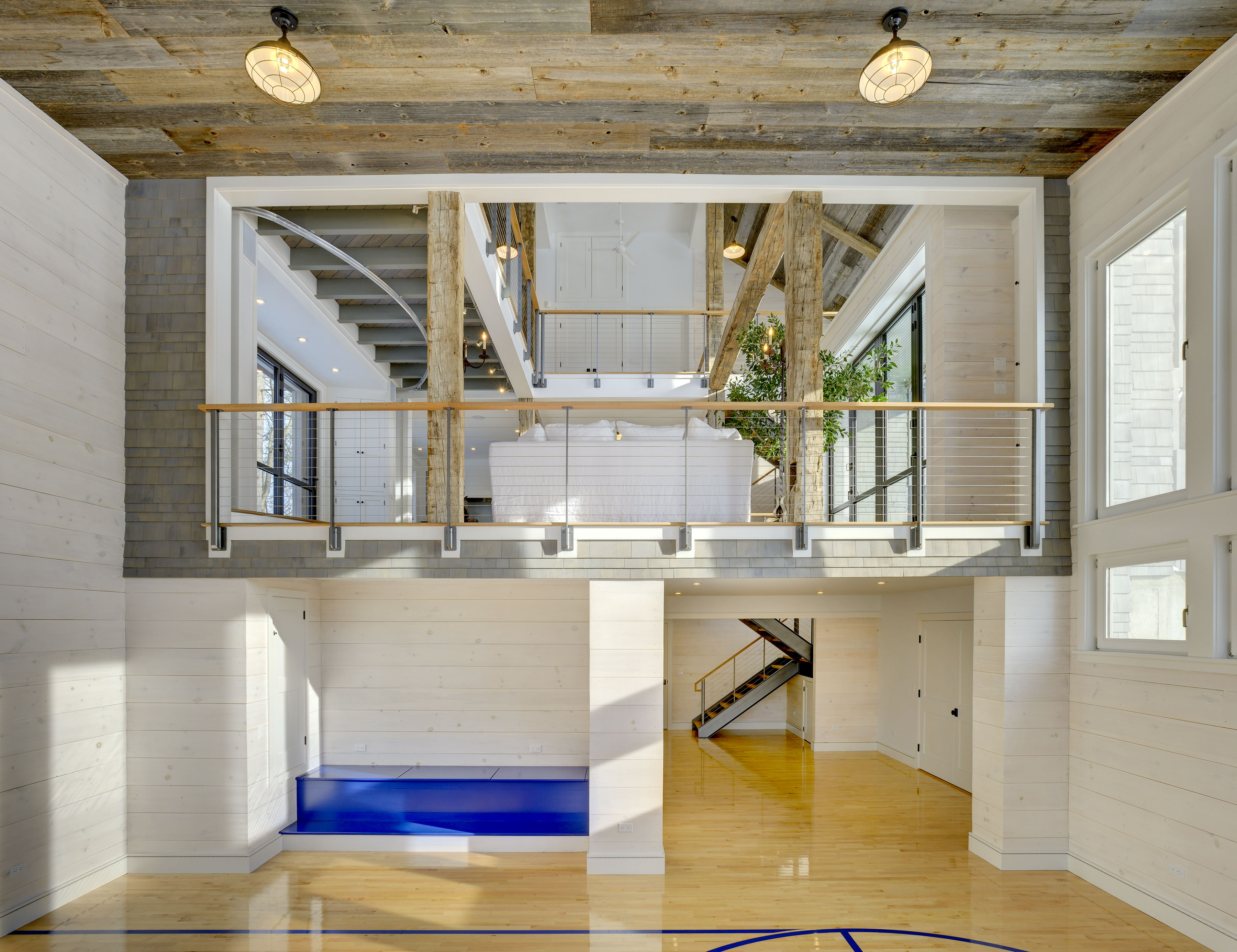 Indoor basketball court and reclaimed wood ceilings with keuka cable railing overlook