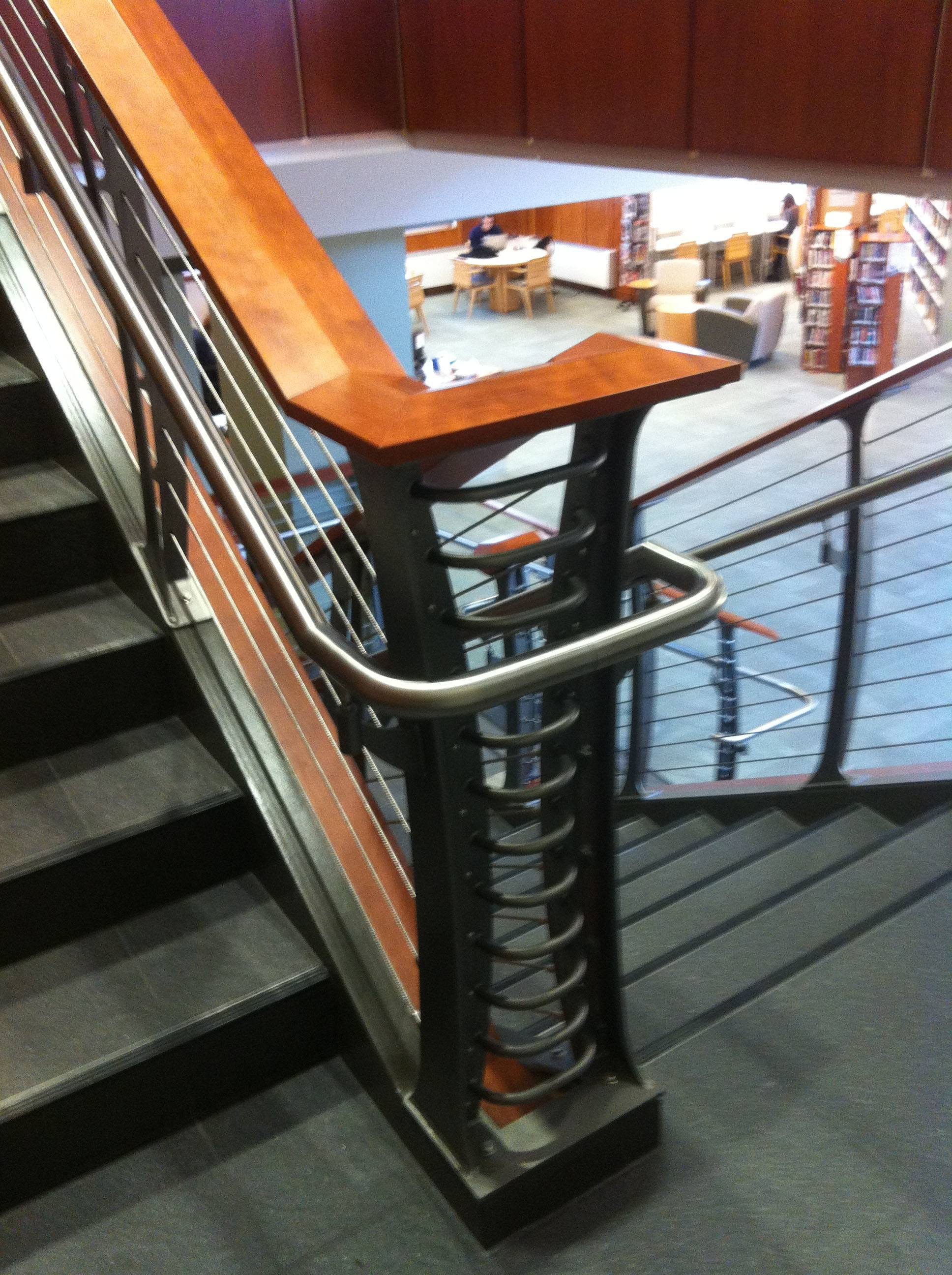 Keuka cable railing with stainless handrail, cherry banister and concrete staircase