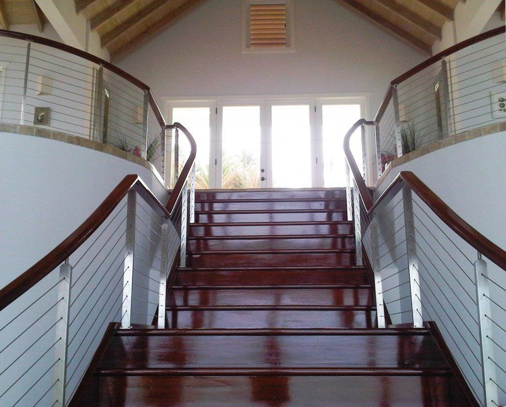 Antigua custom cable railing for interior staircase. Stainless steel stair railings with mahogany steps.