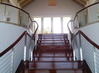 Located in Antigua Keuka Studios created this custom stainless steel railing on this grand interior staircase