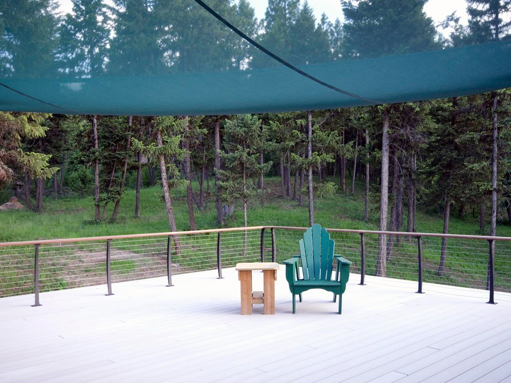 Outdoor deck featuring composite deck, sail shade and stainless cable railing