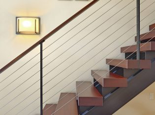 Sconce lighting on floating staircase with cherry wood treads