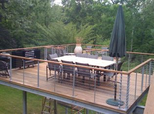 Simple aand Clean Lines Cable Railing For This Uniqued Deck Dining Area