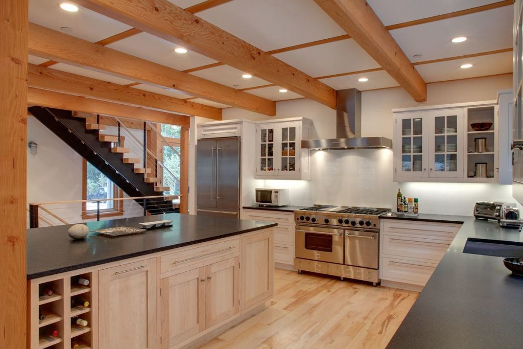 Large and spacious gourmet kitchen with heavy wood ceiling beams.