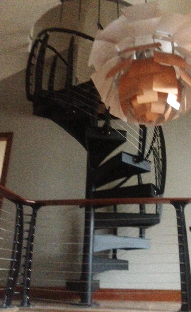 Modern spiral staircase with matching cable railing from below