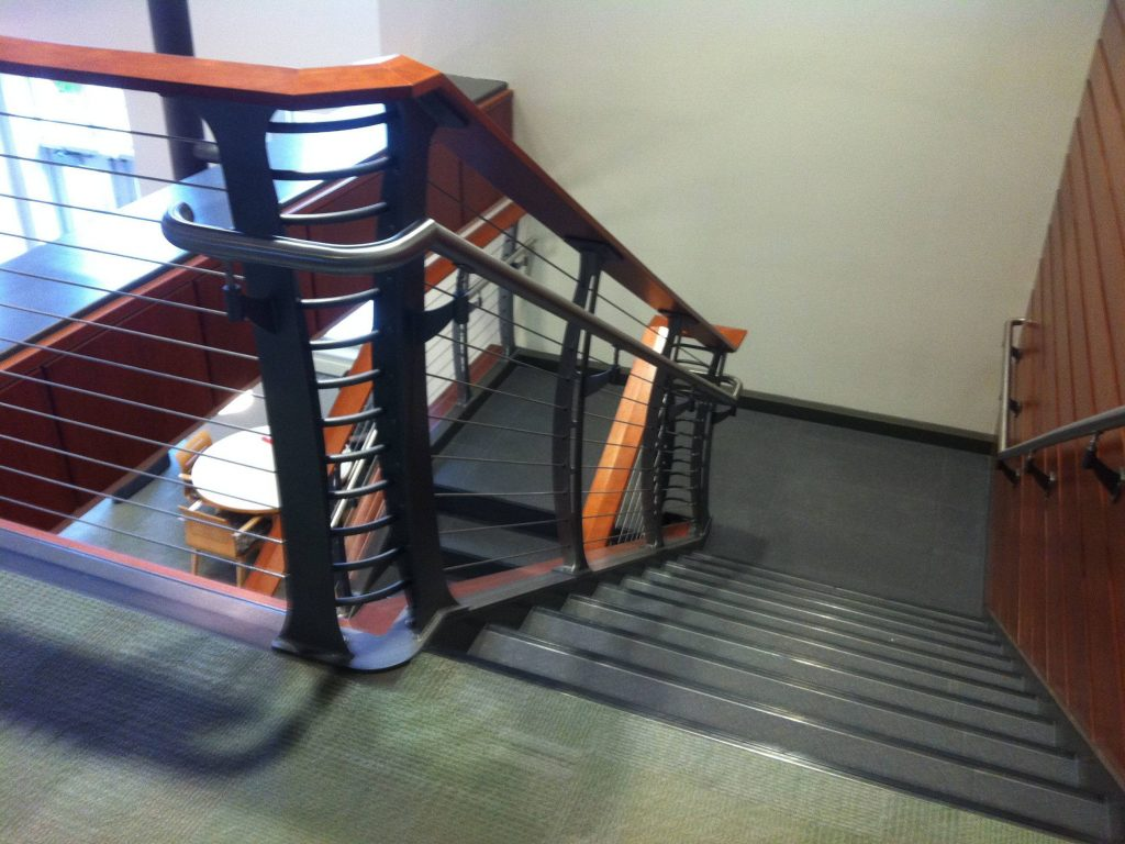 Stainless steel handrail on both sides of the staircase designed to meet the albany college requirements