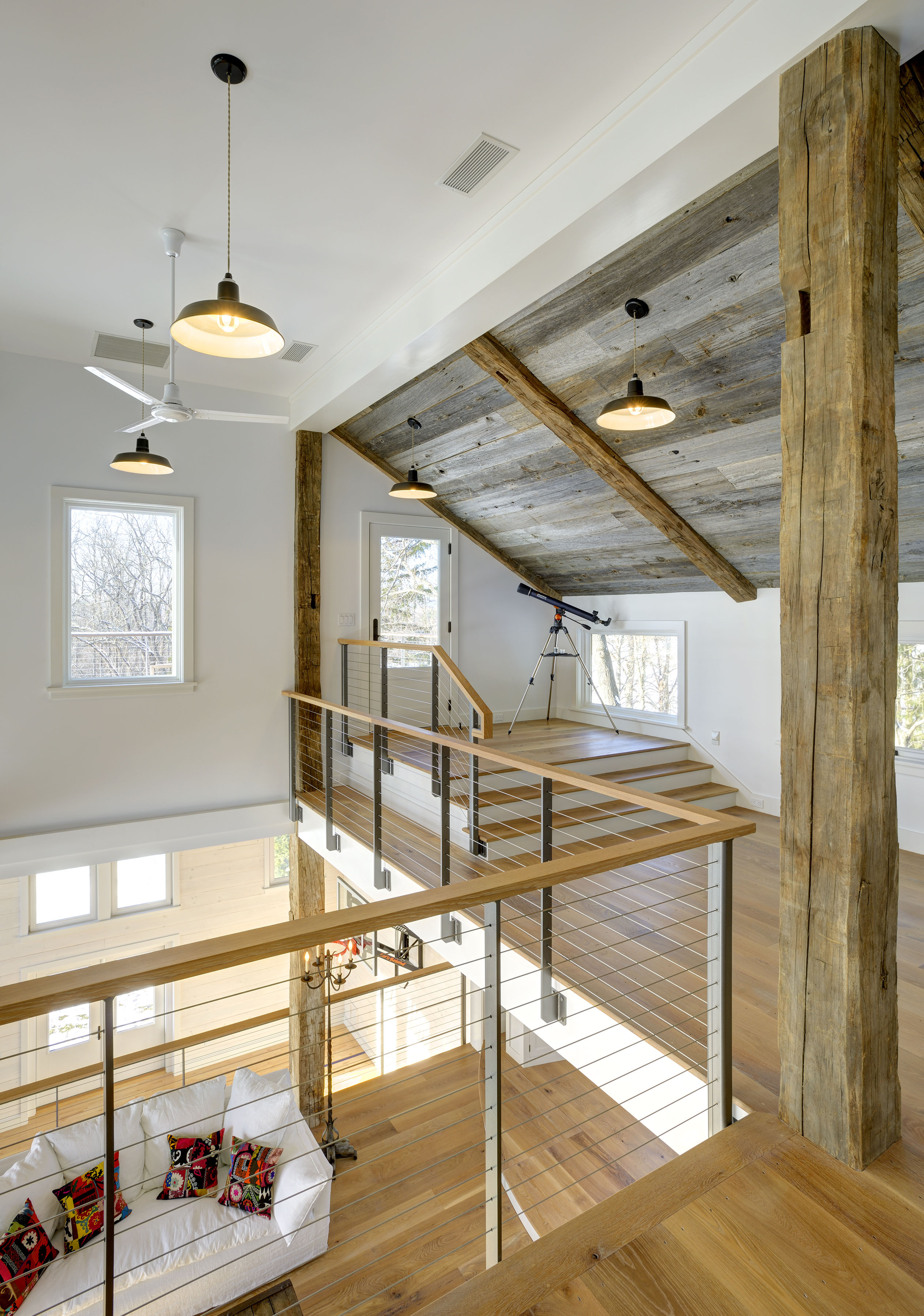 Stainless steel ithaca style cable railing on the loft looking over the living space