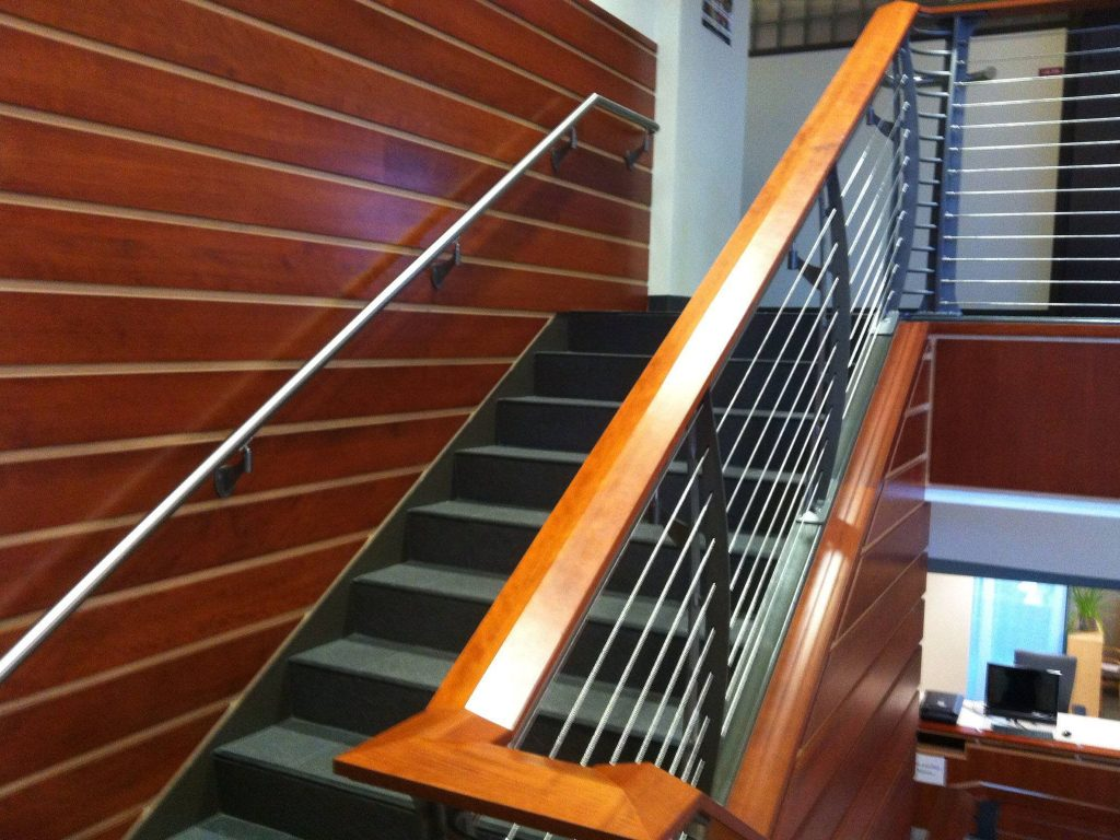 Teak and holly looking wall paneling accent this  staircase with a cherry banister