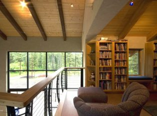 Upstairs loft with keuka cable railing overlooking living room and outdoor view