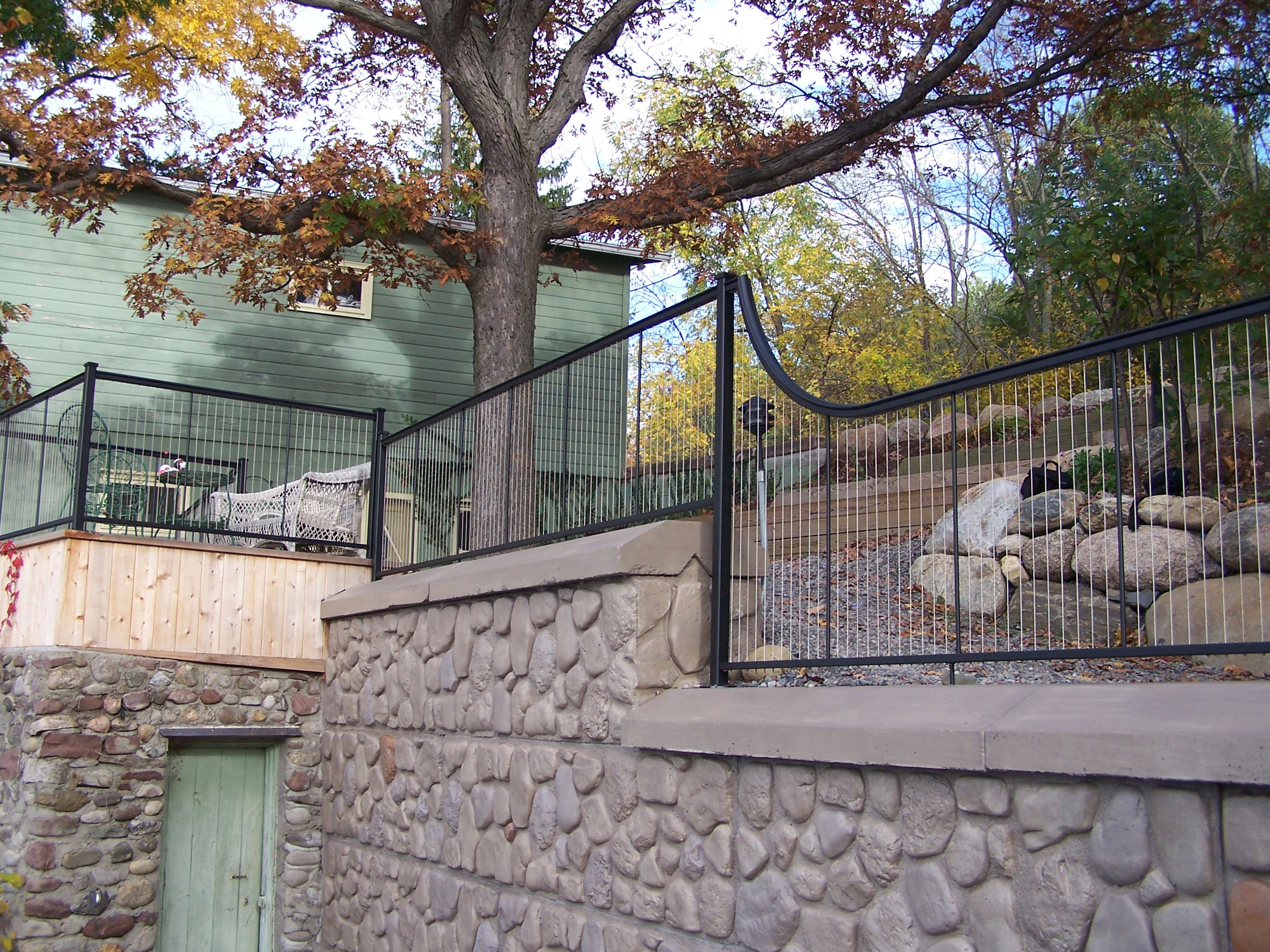 Vertical cable railing outdoor on stone retaining wall