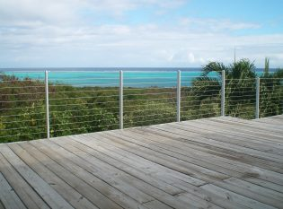 View of turquoise sea through cable railing