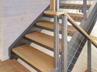 Wood handrail detail on this landing with stainless steel cables