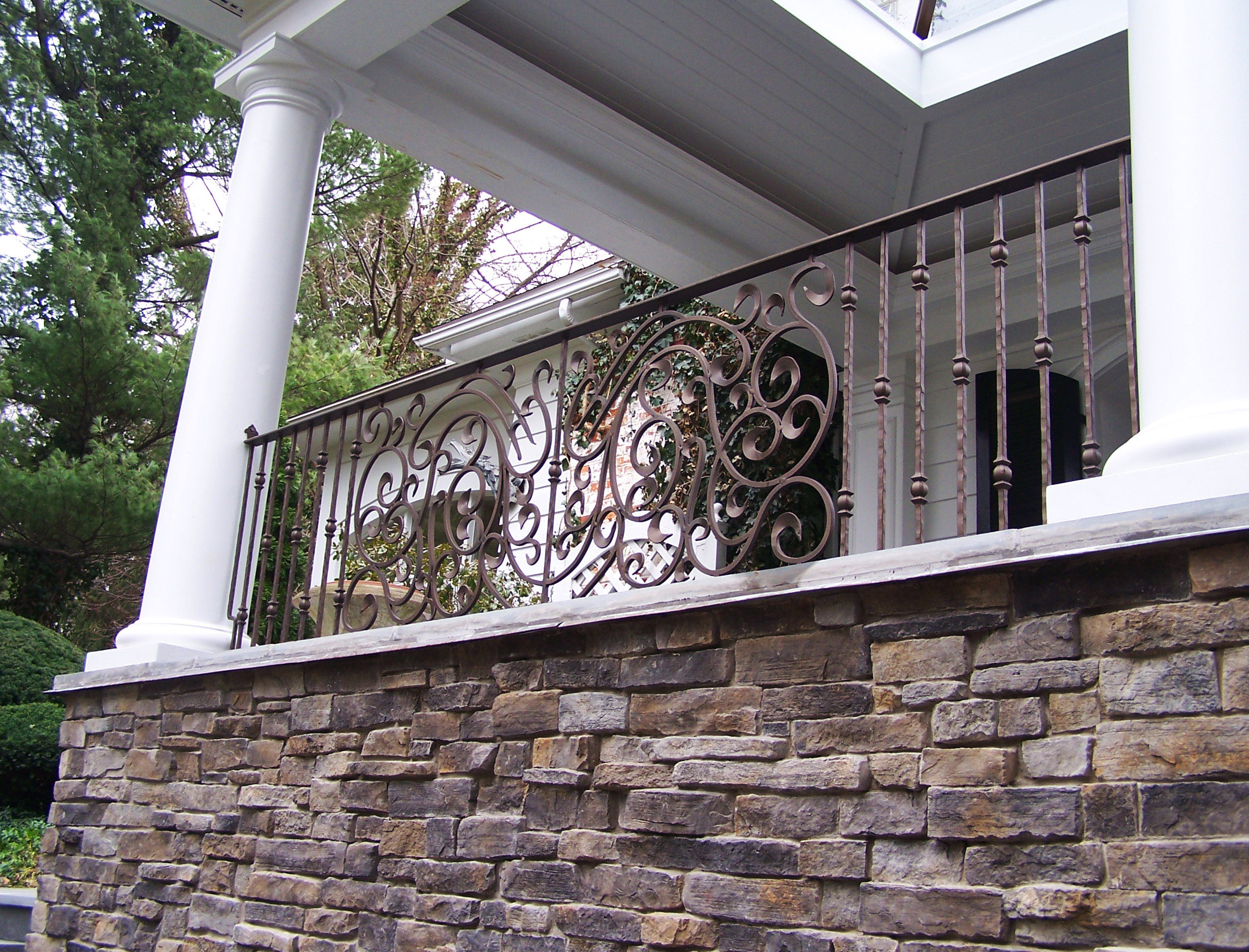 Wrought iron porch railing set between roman tuscan columns