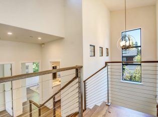 Multi-level stainless steel cable railing stair with oak wood top rail