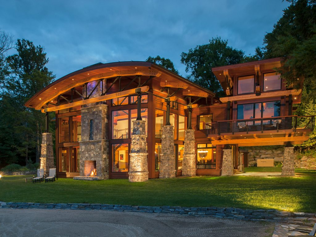 Adirondack mountain home with curved glulam beams and outdoor fireplace