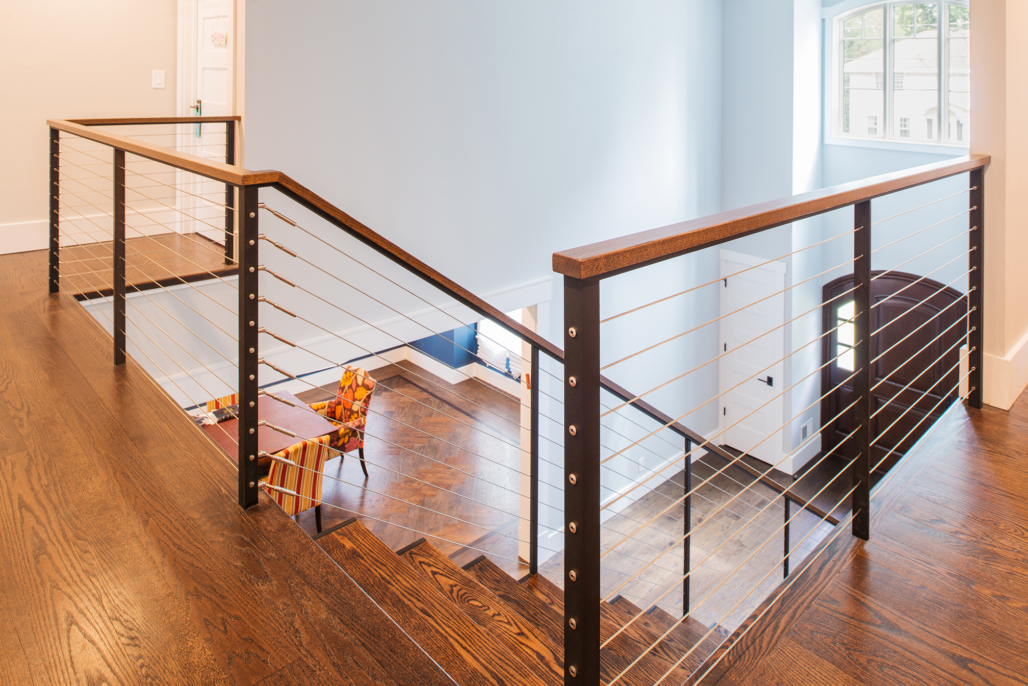 Second level foyer entry with cable railings and staircase.