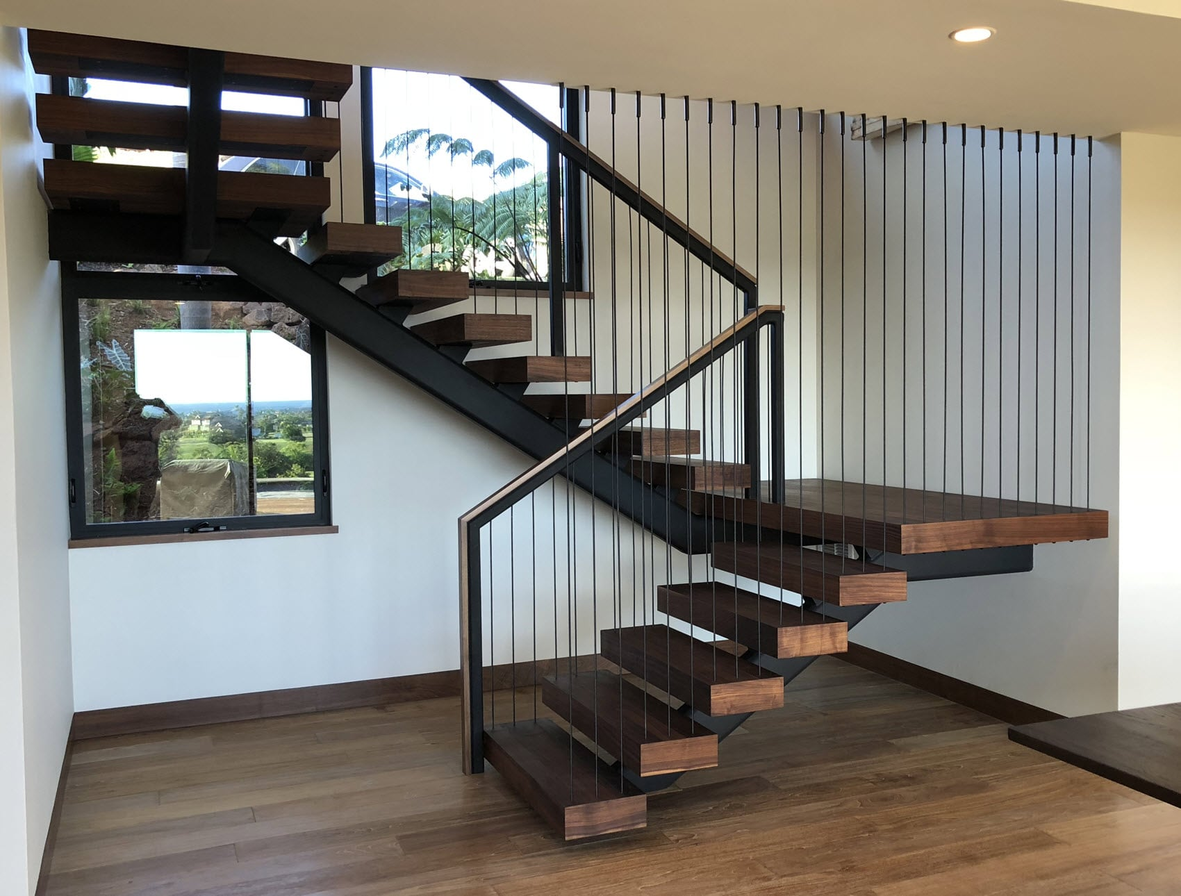 Open Staircase with blackened vertical cables.