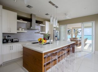 Open white kitchen leading to outdoor dining area.