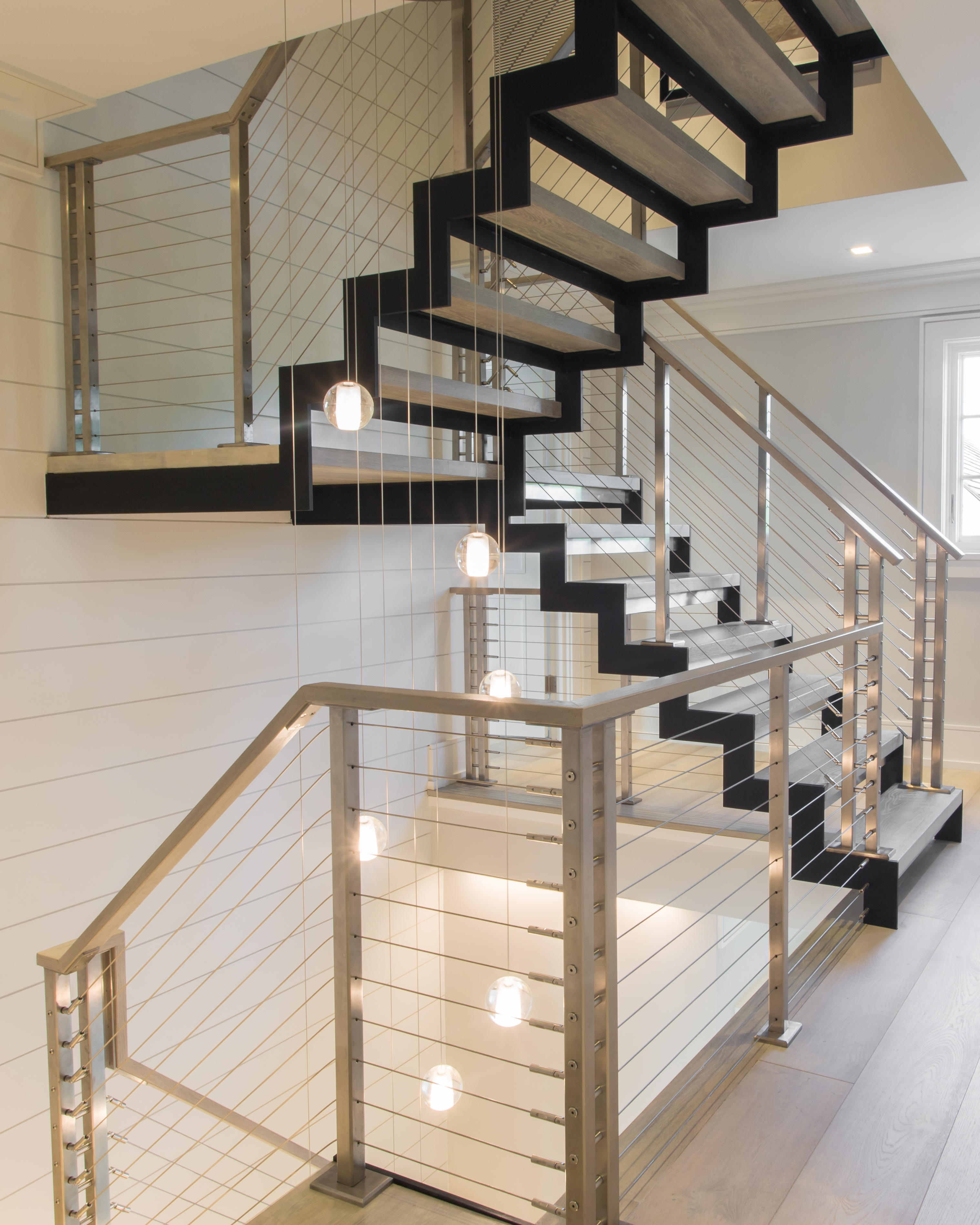 Floating modern staircase with zig zag stringers and stainless steel cable railing