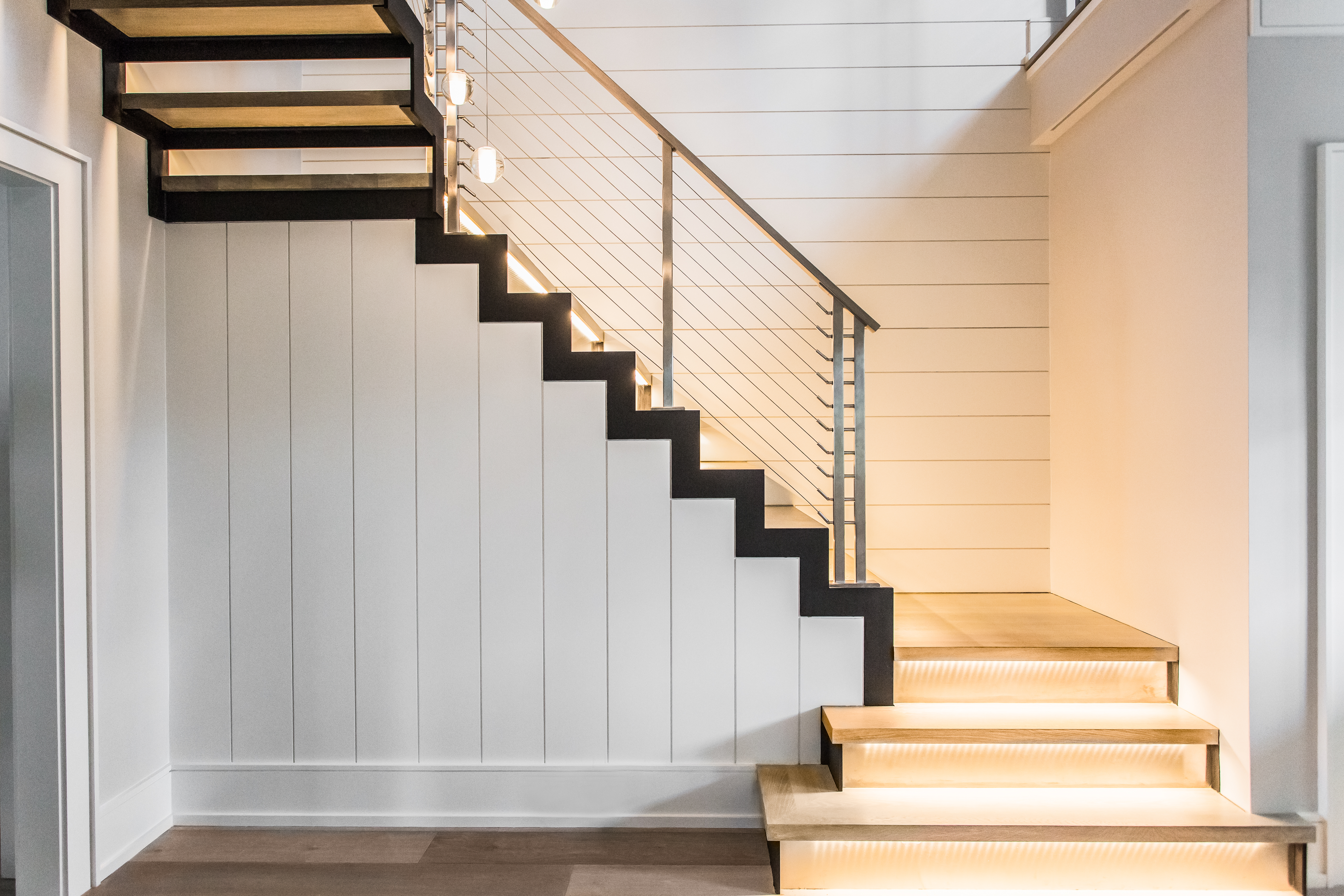 Modern staircase with floating stairs and wood landing