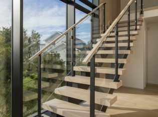 Modern glass staircase railing and floor to ceiling wall of glass