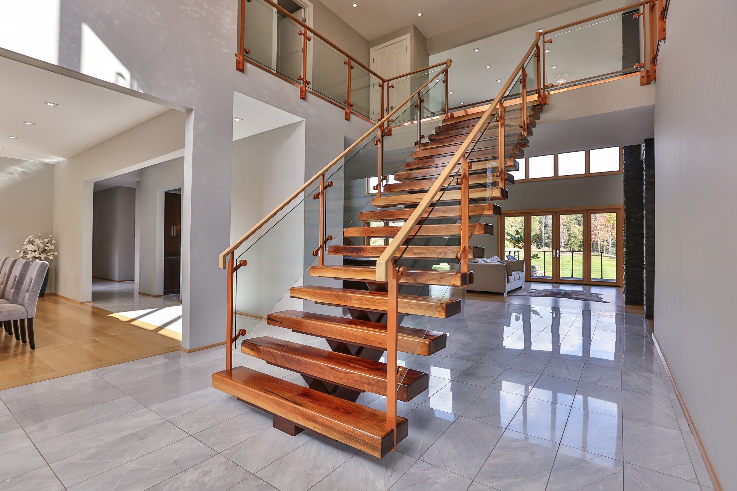 Wide mono-stringer staircase with glass railing.