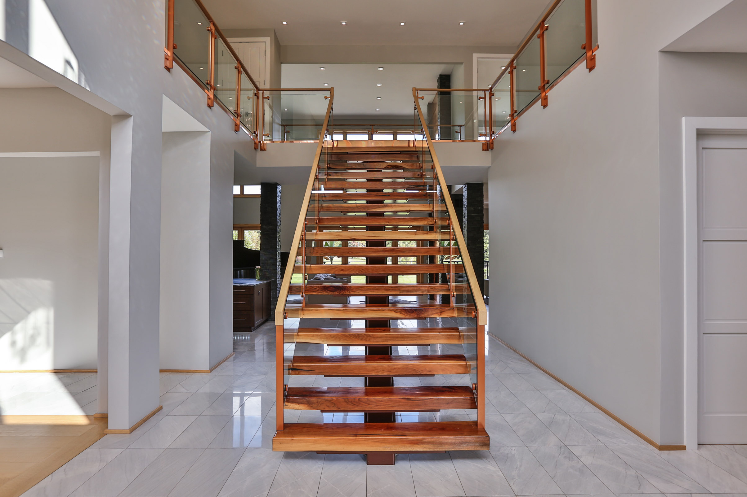 Floating mono stringer staircase with glass railing