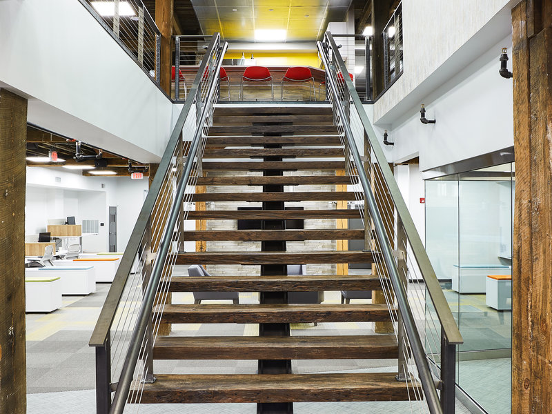 Reclaimed padauk wood and steel mono-stringer staircase.