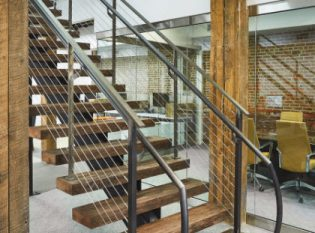 Custom mono-stringer staircase with reclaimed wood treads and clear matte coated steel stringer and railing.