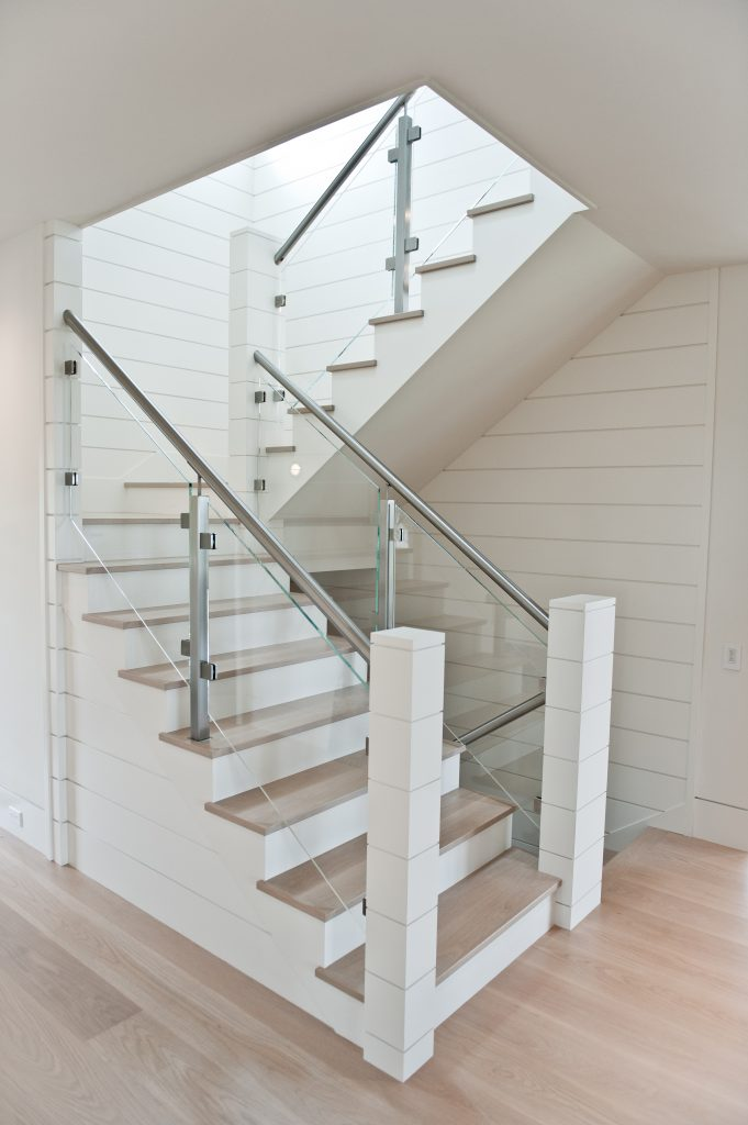 Custom stairs with wood treads, glass railing, and custom posts