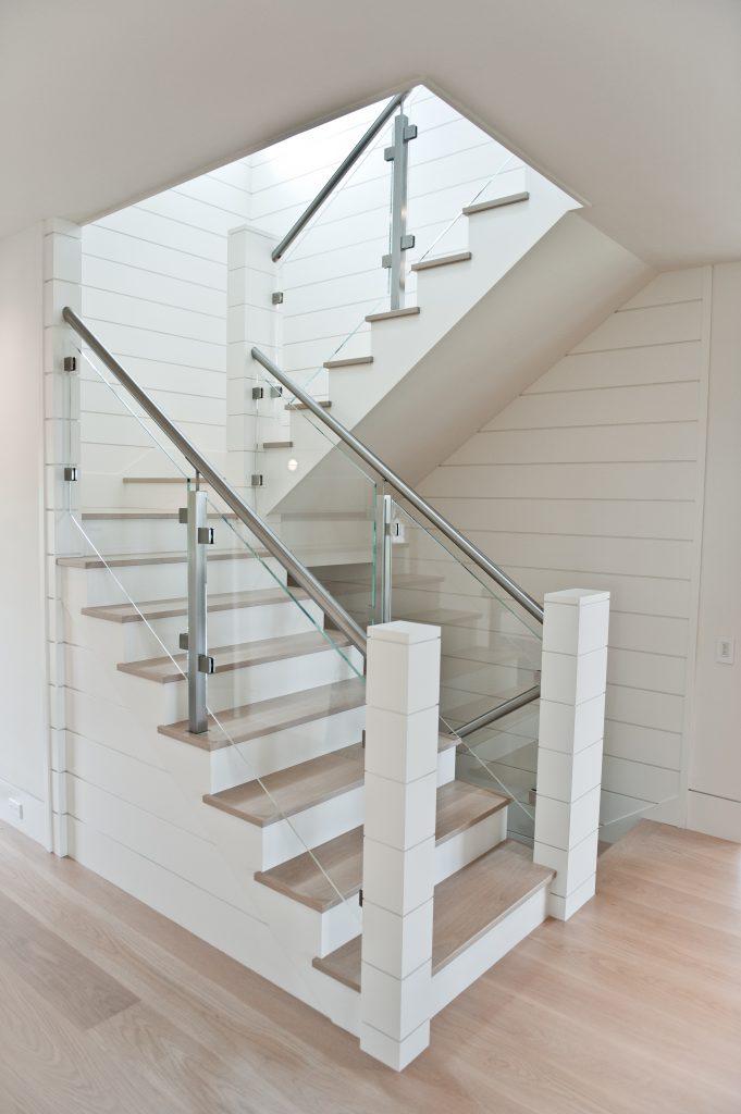 Custom stairs with wood treads, glass railing, and custom posts