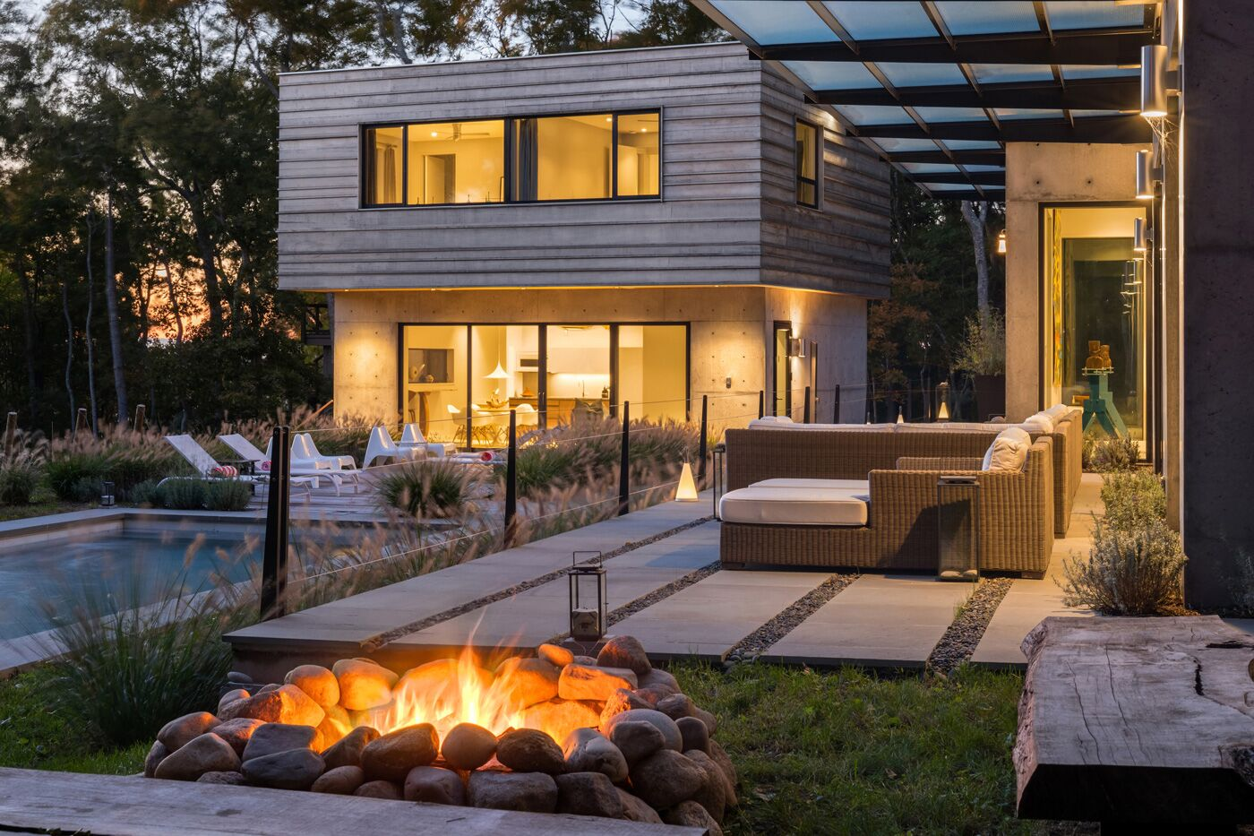 Evening campfire with stone patio and cable railing