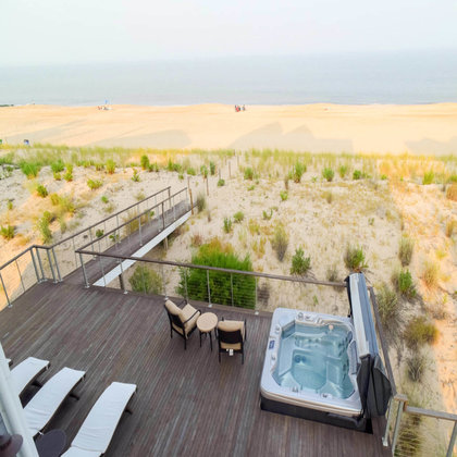 Large deck facing the beach with cable railing, hot tub, and lounge area.