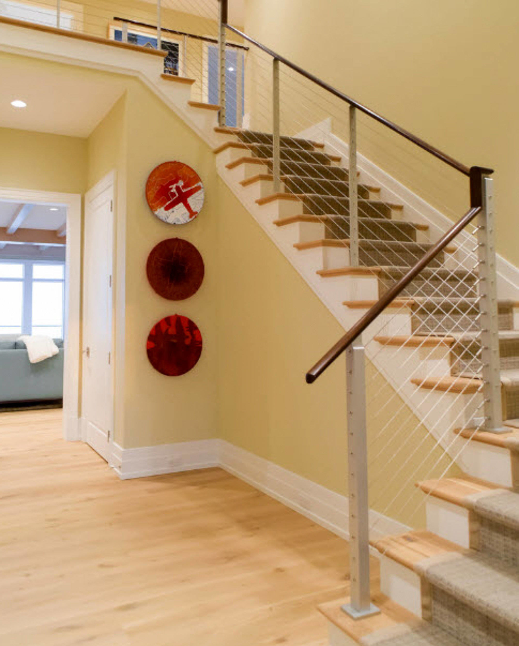 Beach house interior stairs with cable railing and dark wood top rail.
