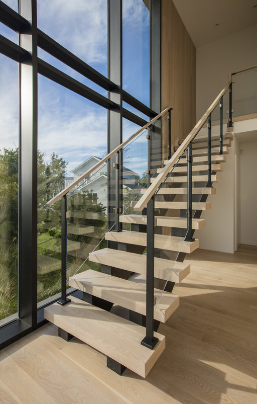 Modern floating staircase with glass infill railing.