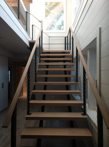 Custom straight staircase with light wood hand rail and treads