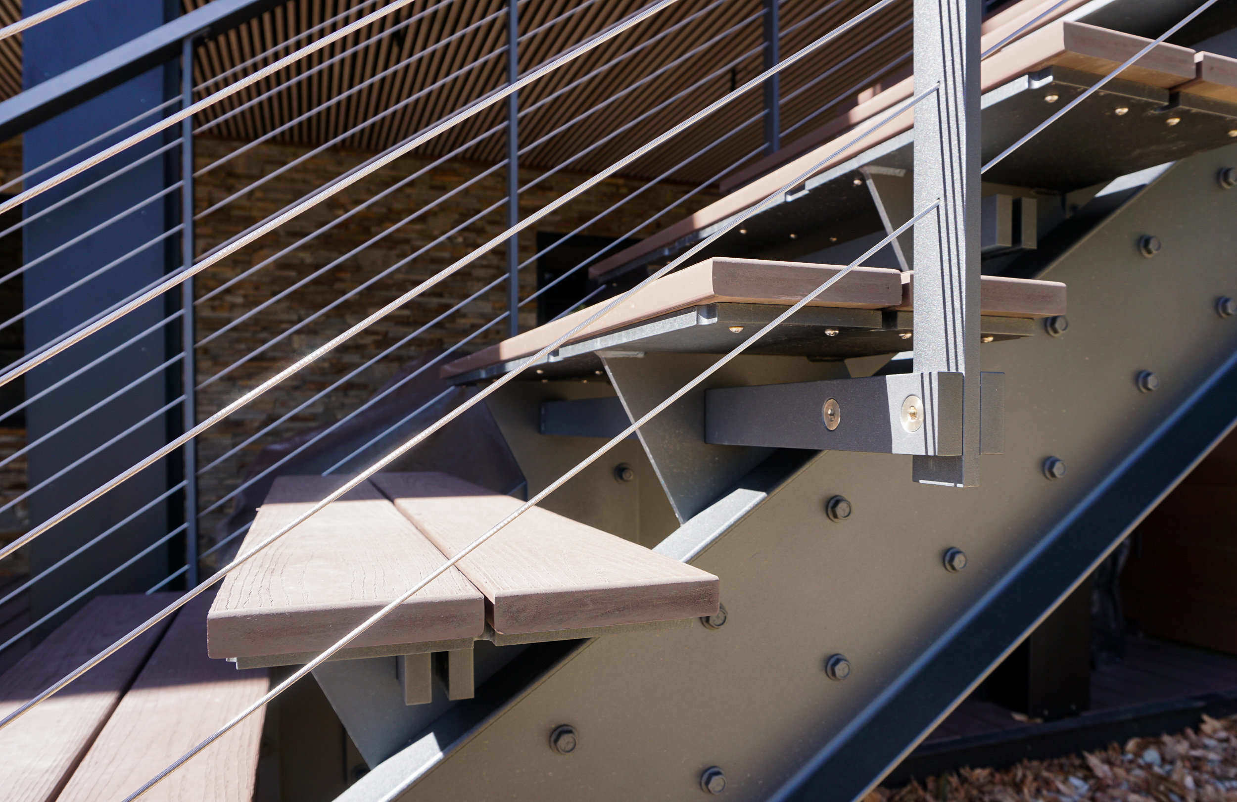 Steel stringer staircase with exposed hardware railing system