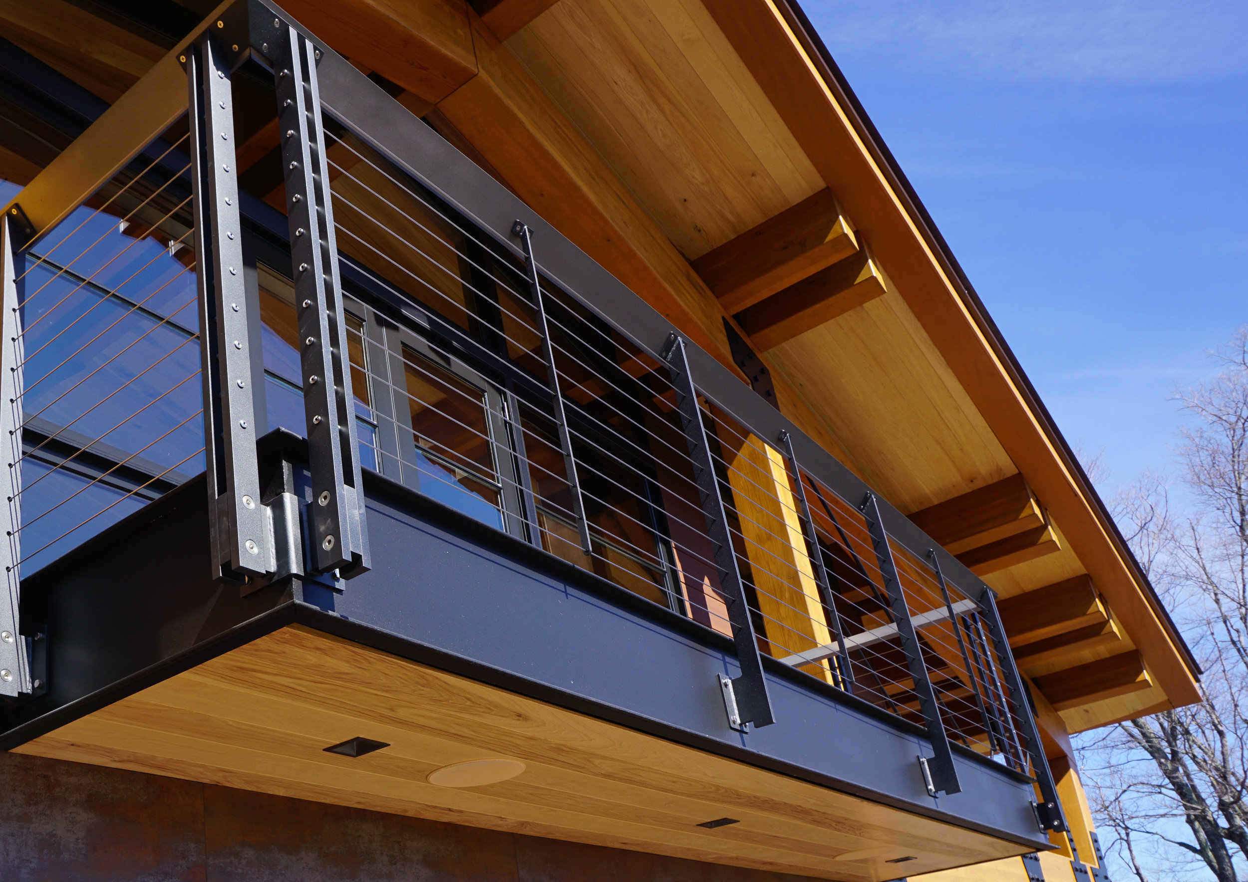 Custom fascia-mounted cable railing on timber frame home