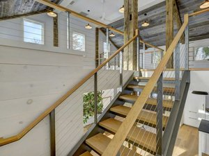 Exposed beam interior with cable railing and floating stairs