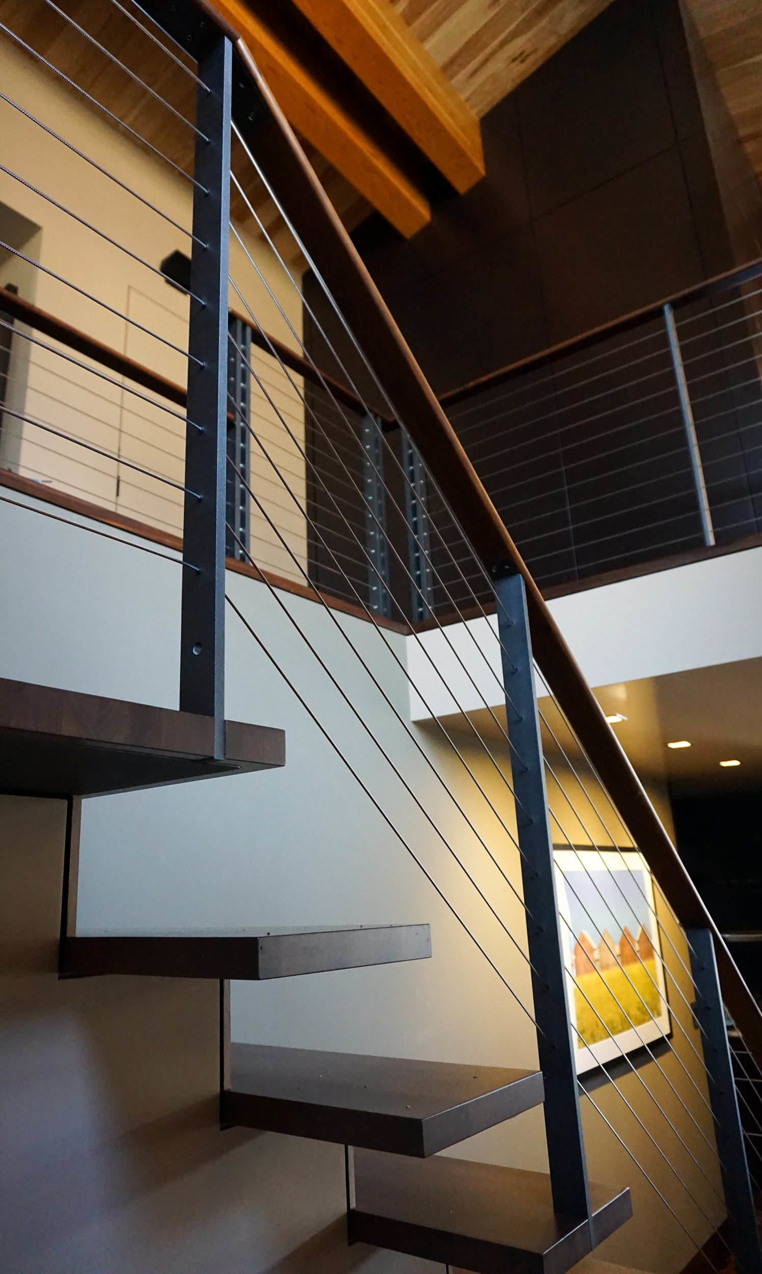 Interior staircase cable railing with custom posts and wood top rail