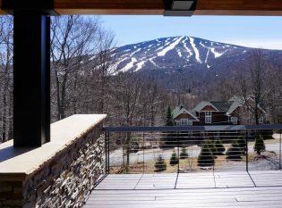 View of snowy Vermont mountains from large cable railing deck