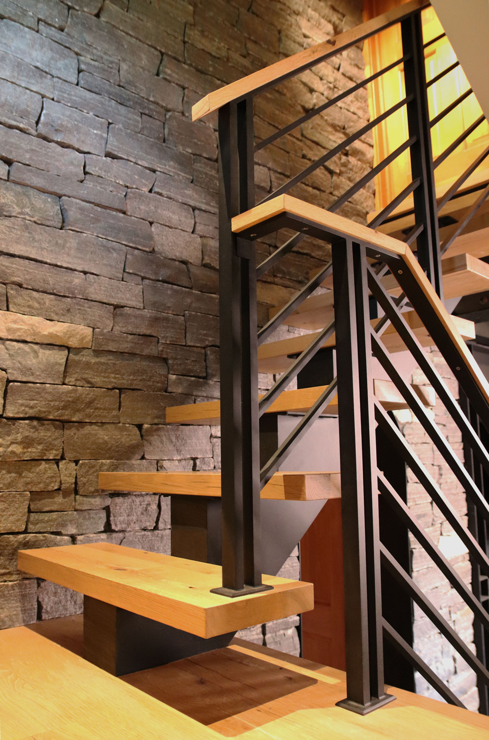 Floating staircase with modern flat bar railing.